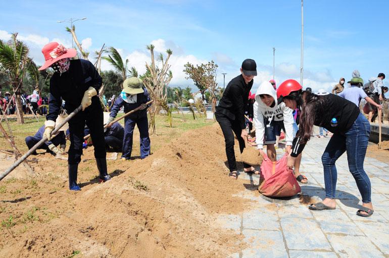 Sinh viên Trường cao đẳng Y tế Phú Yên làm vệ sinh, nạo vét cát tại khu vực đi bộ đường Độc Lập sau cơn bão số 12 - Ảnh: TRUNG HIẾU